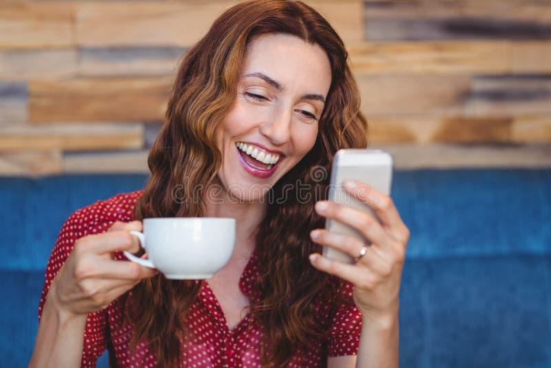 Download Femme à L'aide De Son Téléphone Portable Et Tenant La Tasse De Café Photo stock - Image du femelle, séance: 56486442