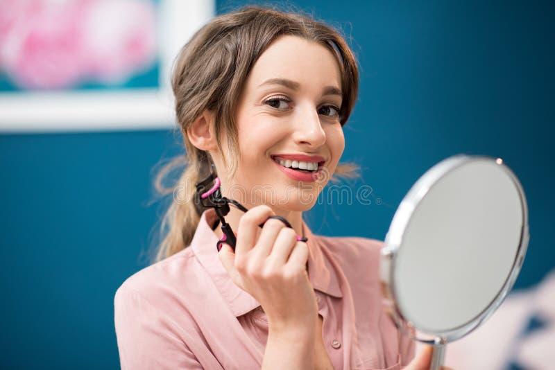 Femme à l'aide du bigoudi de cil photo stock
