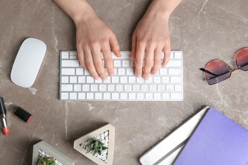 Femme à l'aide du clavier à la table de marbre photographie stock libre de droits