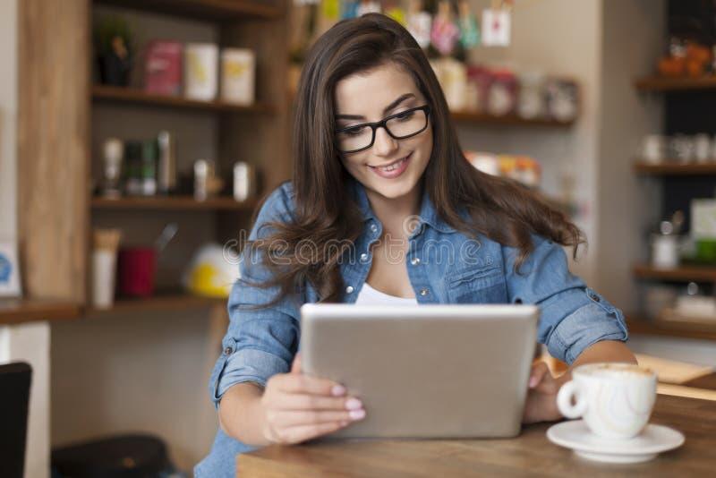 Femme à l'aide du comprimé en café images libres de droits