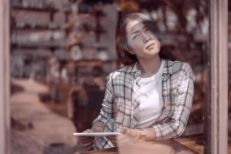 Femme à l'aide du comprimé numérique et pensant en café images stock