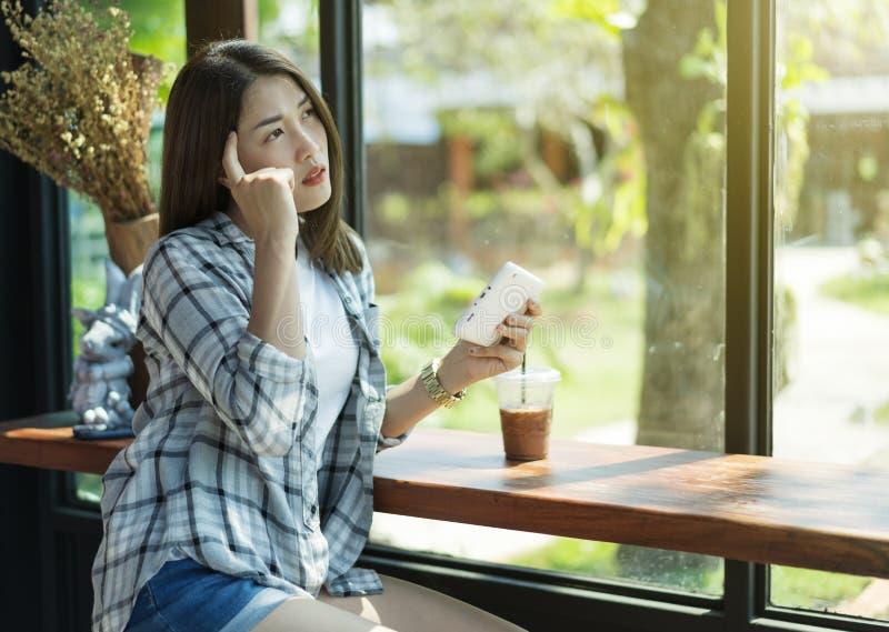 Femme à l'aide du comprimé numérique et pensant en café image stock