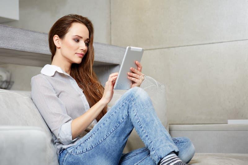 Femme à l'aide du comprimé numérique sur le sofa photographie stock
