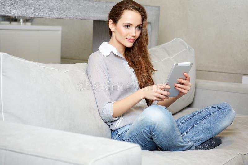 Femme à l'aide du comprimé numérique sur le sofa photo libre de droits