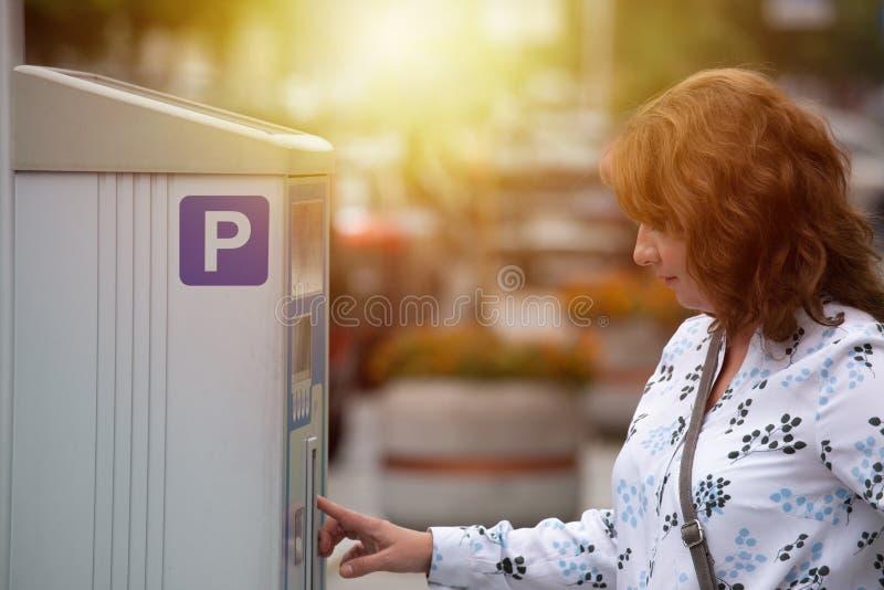Femme à l'aide du parcomètre photo libre de droits