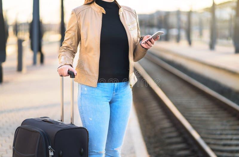 Femme à l'aide du smartphone dans la station de train tout en attendant photo stock