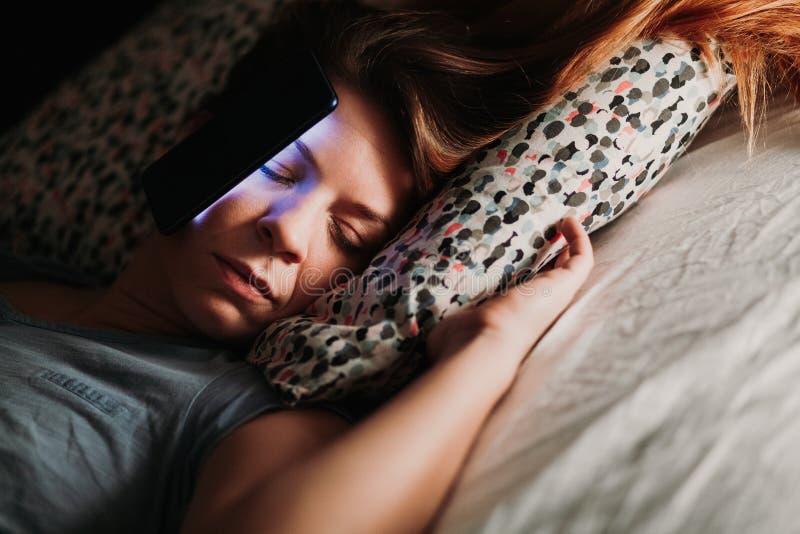 Femme à l'aide du smartphone dans le lit la nuit images stock