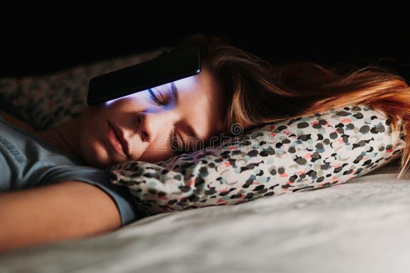 Femme à l'aide du smartphone dans le lit la nuit images libres de droits
