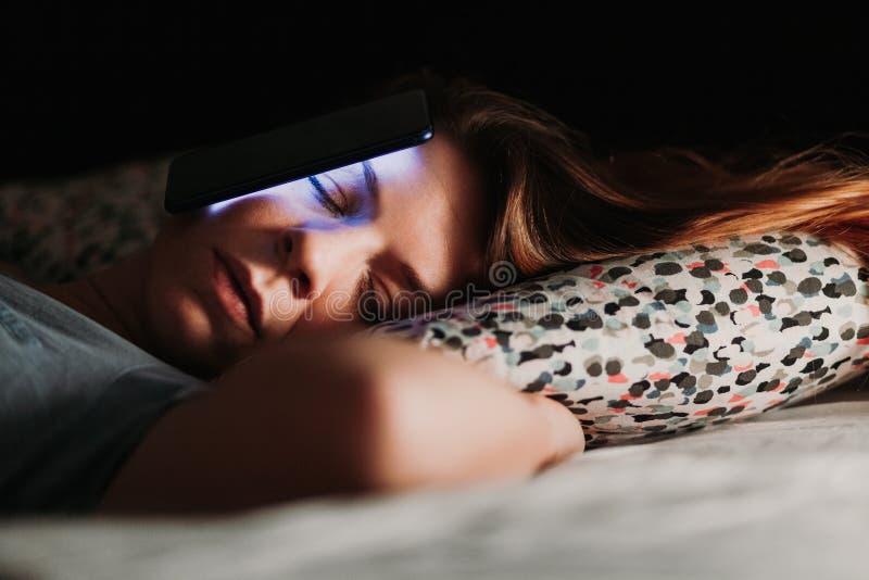 Femme à l'aide du smartphone dans le lit la nuit image libre de droits