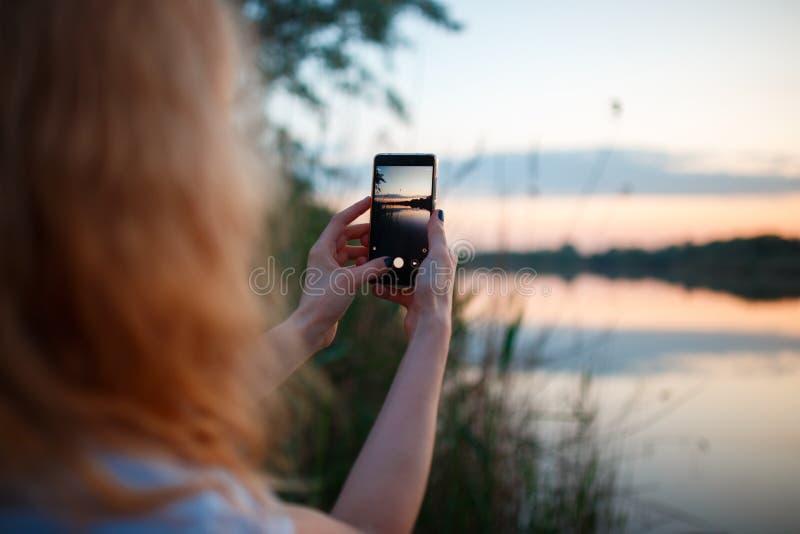 Femme à l'aide du smartphone et prenant la photo du coucher du soleil coloré au-dessus du lac photos stock