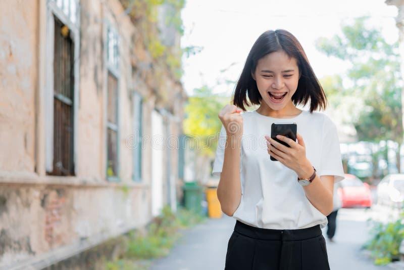 Femme à l'aide du smartphone pour l'application et montrant un geste heureux photos libres de droits