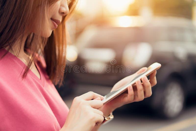 Femme à l'aide du smartphone pour l'application sur le fond de tache floue de voiture photo libre de droits