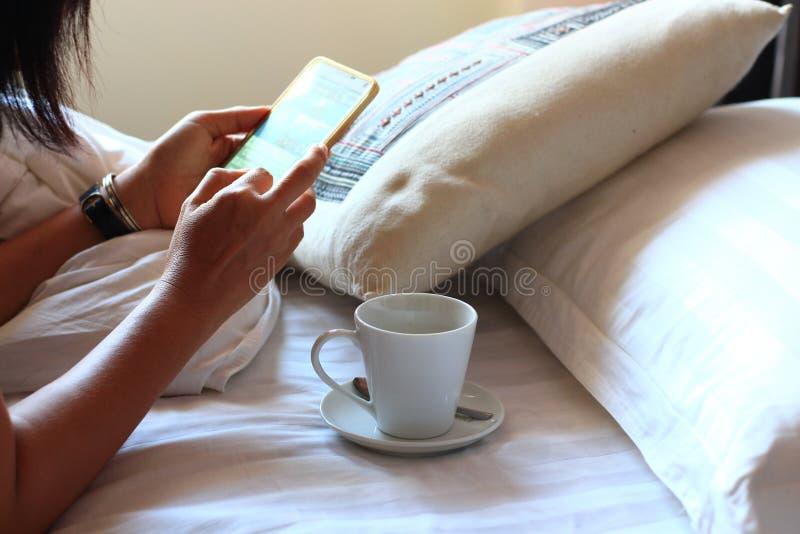 Femme à l'aide du smartphone sur le lit image stock