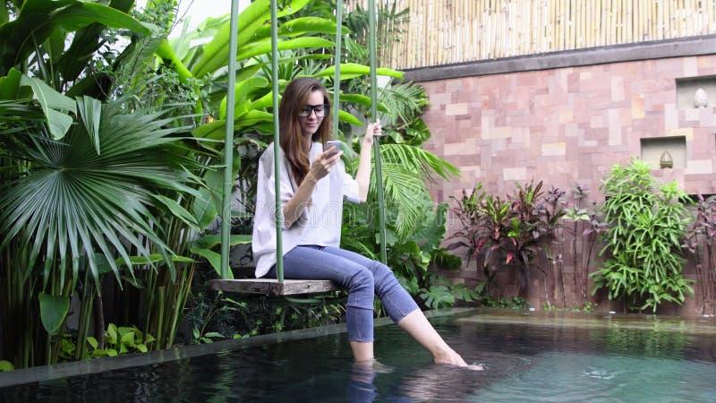 Femme à l'aide du smartphone tout en se reposant sur l'oscillation près de la piscine dans le pays tropical images stock