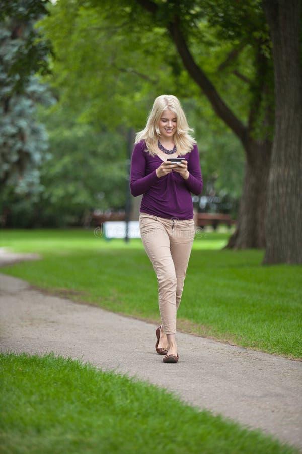 Femme à l'aide du téléphone intelligent dans le parc photo libre de droits