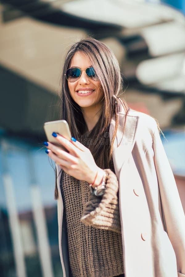 Femme à l'aide du téléphone intelligent dehors images stock
