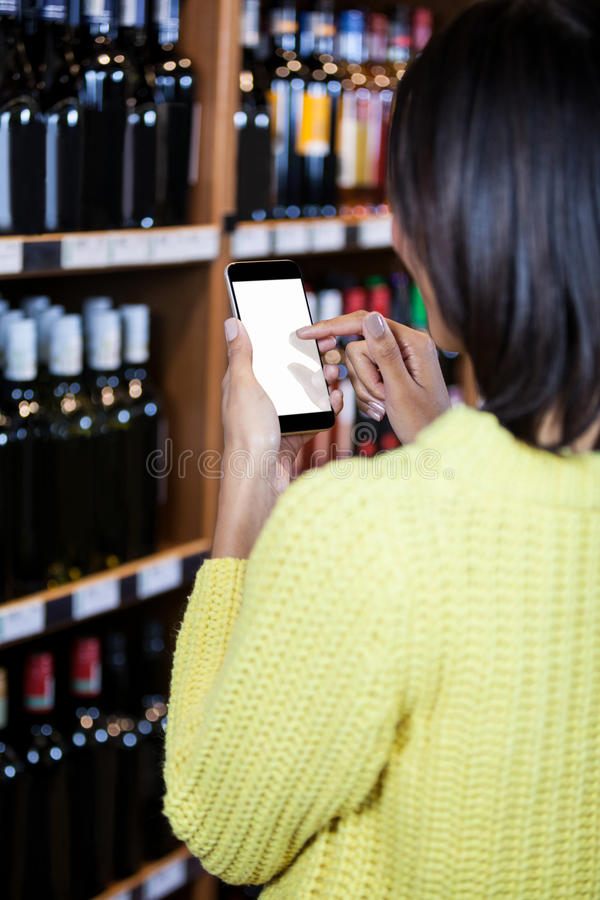Femme à l'aide du téléphone portable dans la section d'épicerie image stock