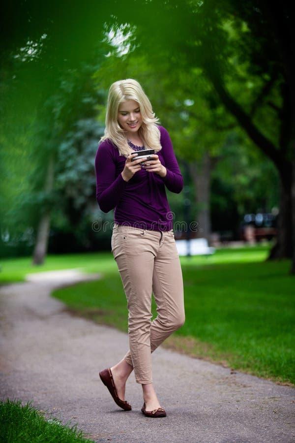 Femme à l'aide du téléphone portable dans le parc photographie stock libre de droits