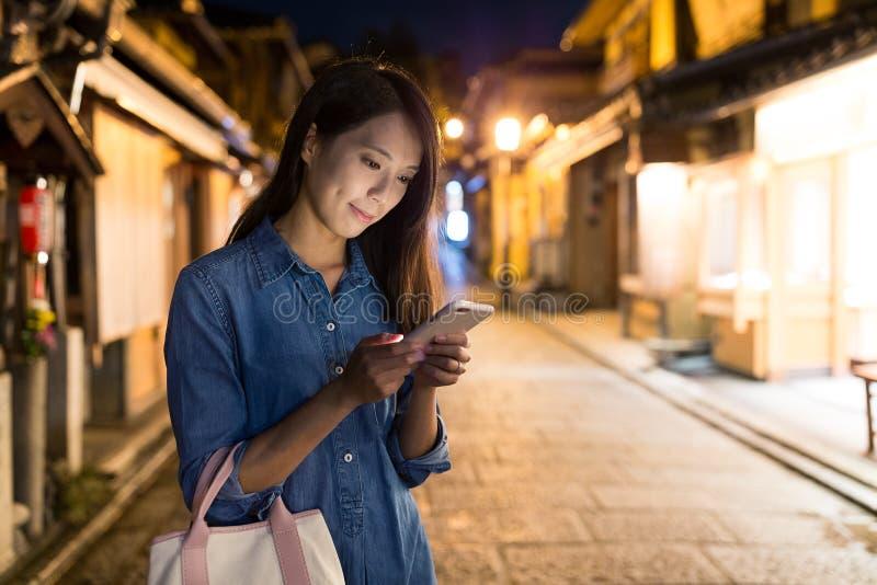 Femme à l'aide du téléphone portable la nuit photographie stock libre de droits