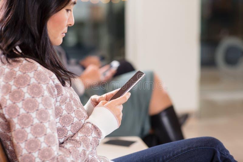 Femme à l'aide du téléphone portable tout en attendant le vol à l'aéroport photo libre de droits