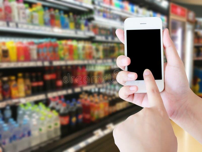 Femme à l'aide du téléphone portable tout en faisant des emplettes dans le supermarché photo libre de droits