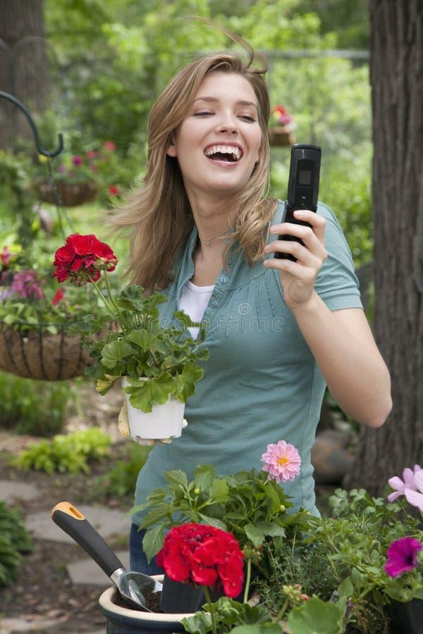 Femme à l'aide du téléphone portable tout en faisant du jardinage photos stock