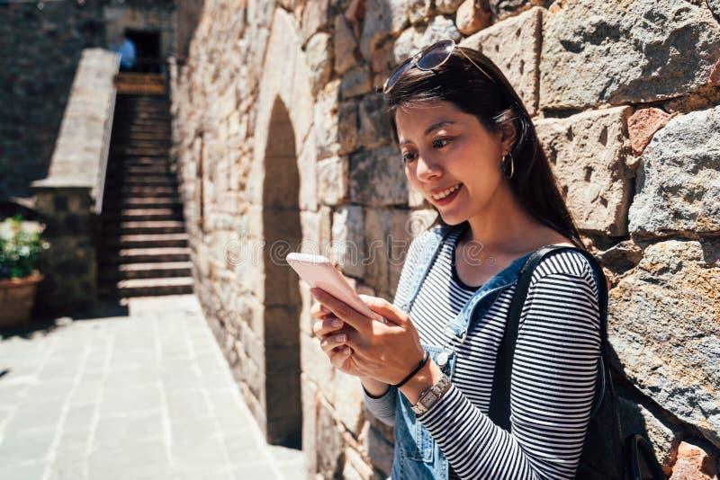 Femme à l'aide du téléphone portable vérifiant l'information photographie stock libre de droits