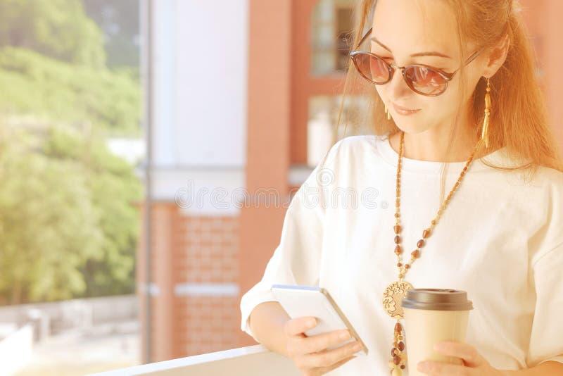 Femme à l'aide du téléphone tout en buvant du café sur le balcon photos libres de droits