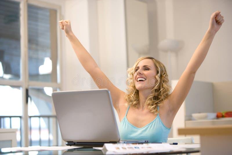 Femme à l'ordinateur portatif avec des bras vers le haut photo stock