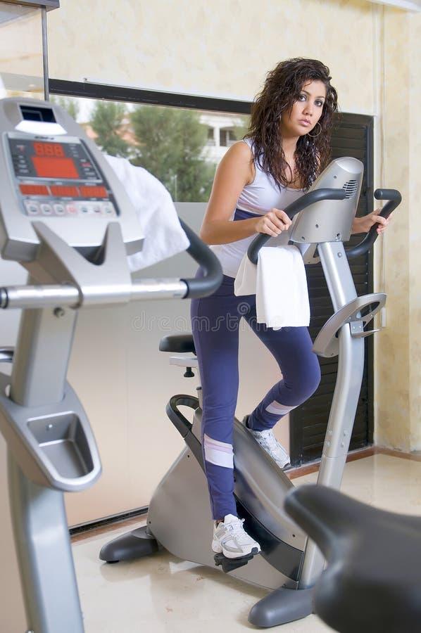 Femme à la gymnastique faisant le cardio- bycicle image libre de droits
