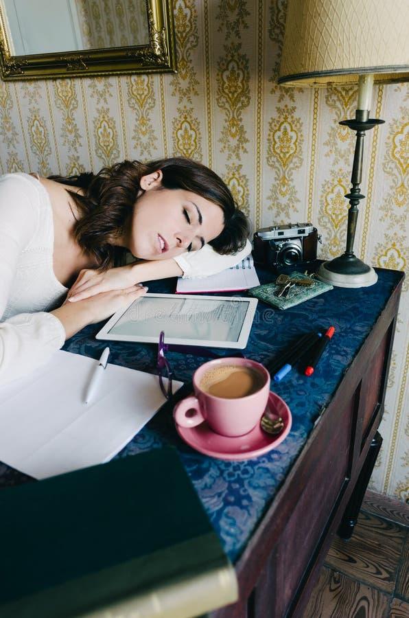 Femme à la maison épuisée de travailleur dormant sur le bureau photos stock