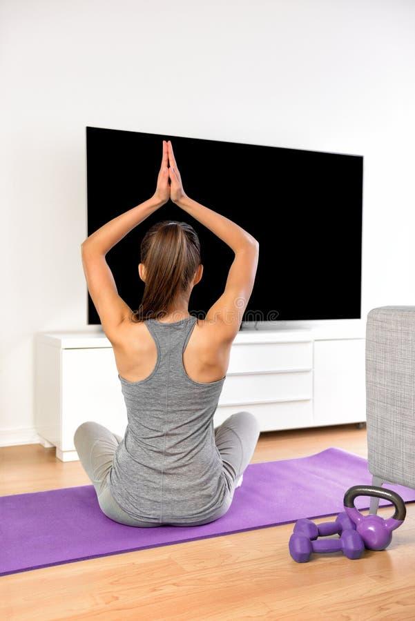Femme à la maison de forme physique faisant l'exercice de yoga regardant la TV image libre de droits