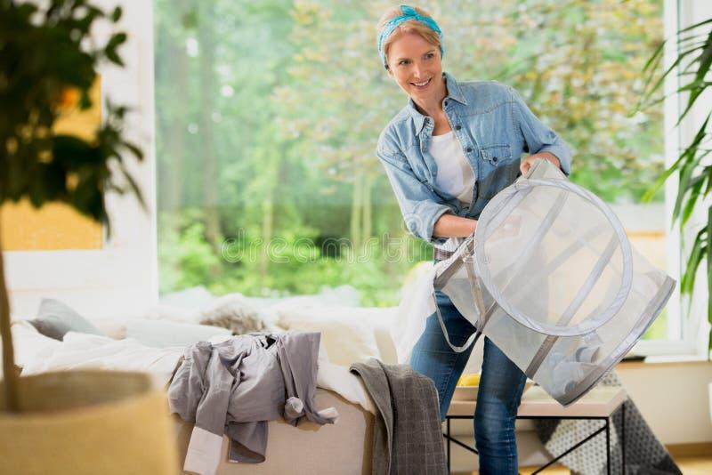 Femme à la maison de service faisant la blanchisserie images stock
