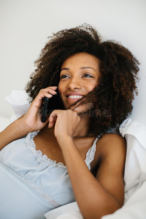 Femme à la maison invitant le smartphone images stock