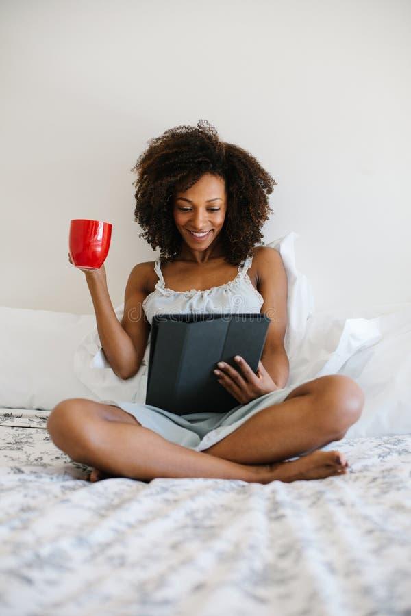 Femme à la maison lisant sur le comprimé numérique photos stock