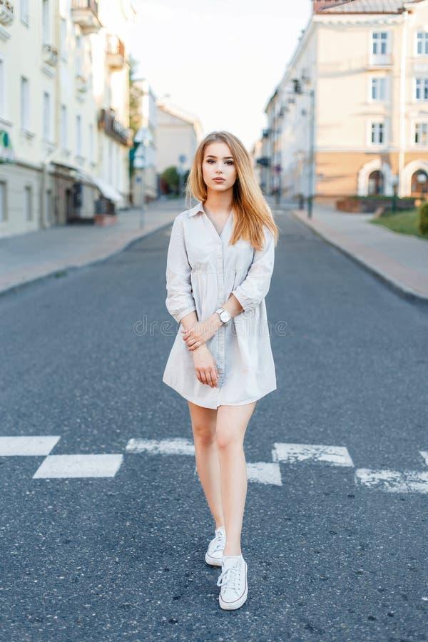Femme à la mode élégante dans une position de robe et d'espadrilles photographie stock