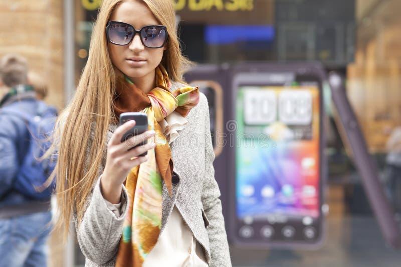 Femme à la mode avec le smartphone sur le public image libre de droits