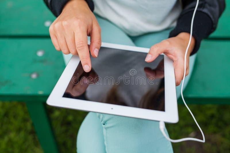 Femme à la mode avec les écouteurs de port de tablette dehors images libres de droits