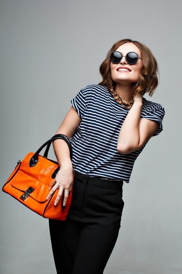Femme à la mode avec un sac orange et de grandes lunettes de soleil rondes image stock