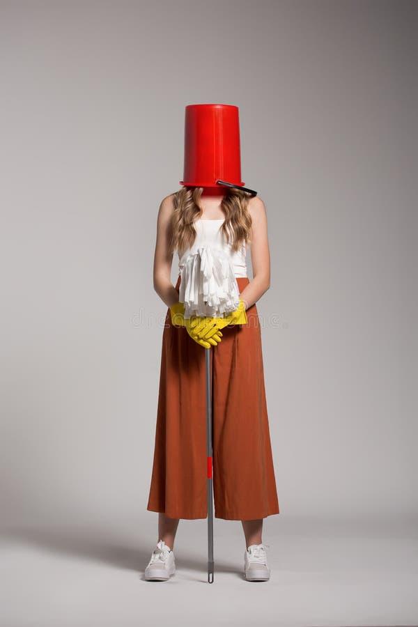 Femme à la mode avec un seau rouge sur sa tête tenant un balai image libre de droits