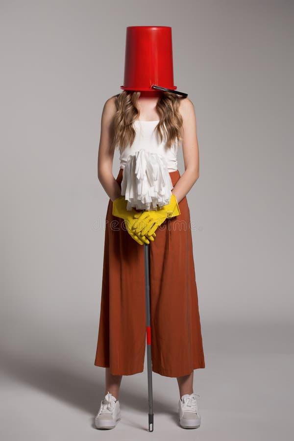 Femme à la mode avec un seau rouge sur sa tête tenant un balai image stock