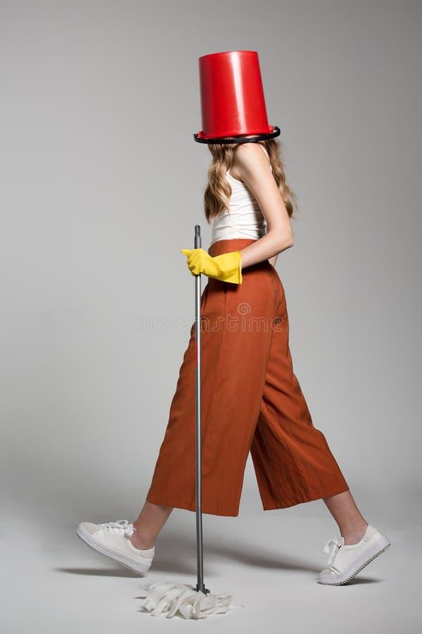 Femme à la mode avec un seau rouge sur sa tête tenant un balai photo libre de droits