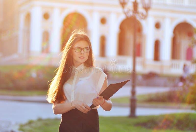Femme à la mode d'affaires tenant un blanc de papier dans des ses mains et posant sur la caméra le processus fonctionnant Portrai image stock
