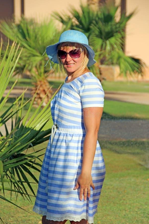 Femme ? la mode dans le chapeau et des lunettes de soleil roses appr?ciant l'achat Fille attirante photographie stock libre de droits