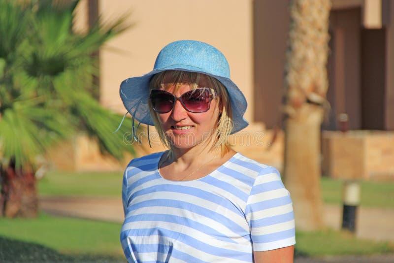 Femme à la mode dans le chapeau rose appréciant la marche le long du parc Fille attirante images libres de droits