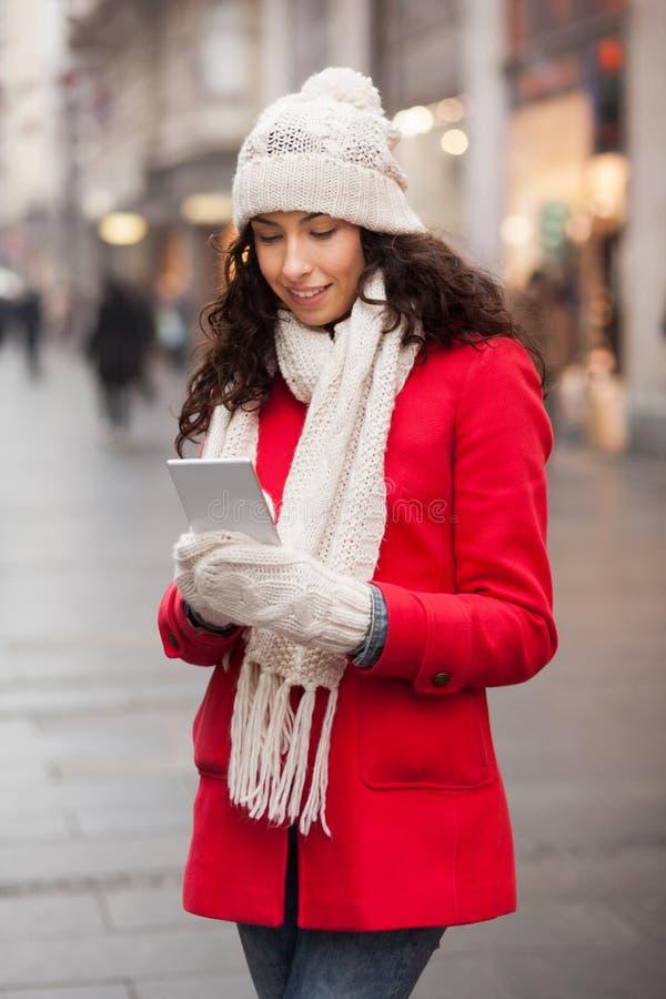 Femme à la mode dans le chapeau rouge de manteau et de laine et gants avec le smartphone en Han photos stock