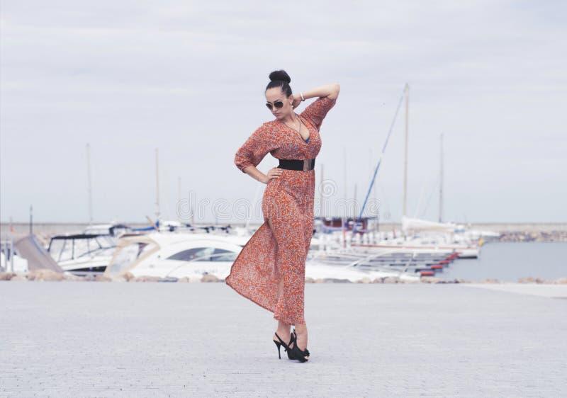 Femme à la mode de brune portant la longue robe dans des lunettes de soleil posant près de la mer, pilier avec des yachts images stock