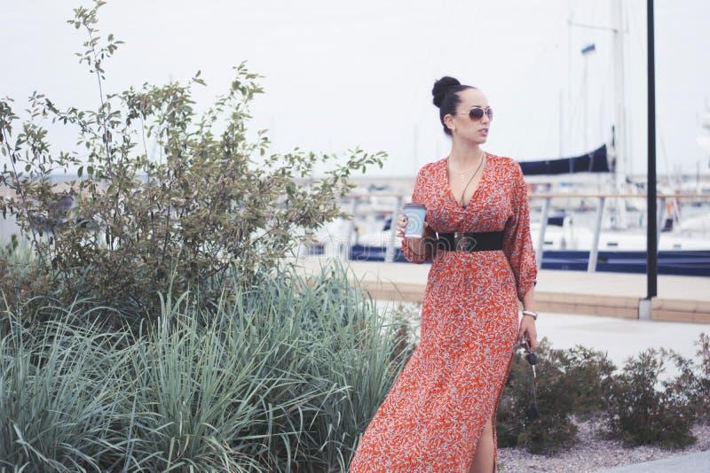 Femme à la mode de brune portant la longue robe rouge dans des lunettes de soleil faisant un tour près de la mer, pilier avec des photo libre de droits