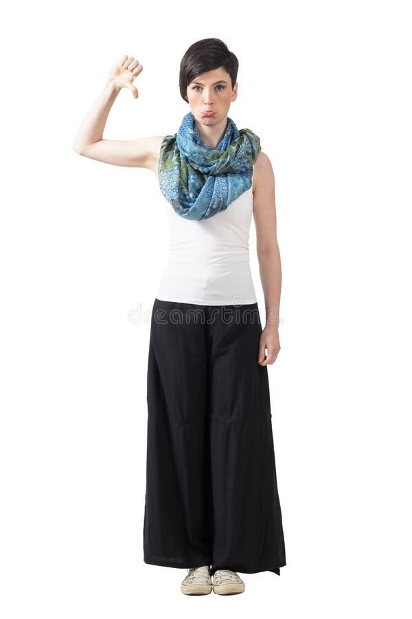 Femme à la mode grincheuse dans le pantalon de large-jambe et foulard avec des pouces vers le bas image stock