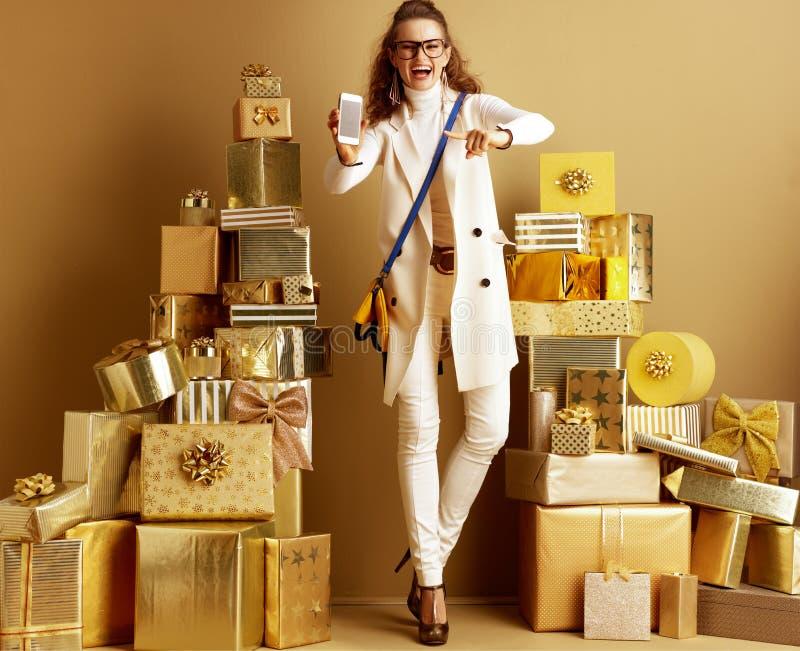 Femme à la mode heureuse de client faisant souffrir à l'écran vide de smartphone images stock